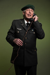 US military general wearing beret. Calling with phone. Studio po