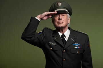 US military general wearing cap. Salutation. Studio portrait.