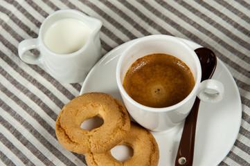 tazzina di caffè, biscotti e un bricchetto di latte