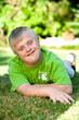 Portrait of handicapped boy on green grass.
