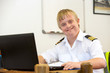 Leinwanddruck Bild - Portrait of young pilot with down syndrome at desk.