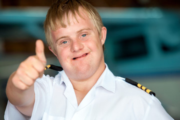Young handicapped pilot showing thumbs up.