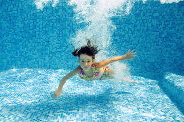 Underwater child in swimming pool, girl swims and having fun