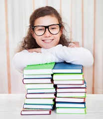 Little girl wearing glasses with pile of books