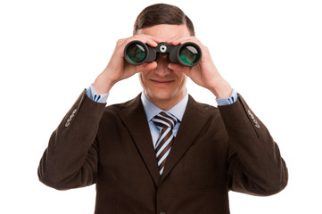 Closeup of a young business man looking through binocular at cam