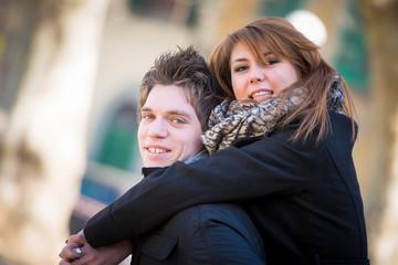 Happy couple piggyback hugging in wintertime park love smiling f
