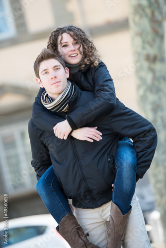 Happy couple piggyback hugging in wintertime park love smiling f