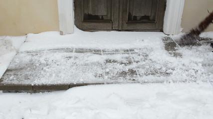 man sweeper clean  broom snow tiles house door entrance