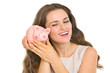 Happy young woman shaking piggy bank