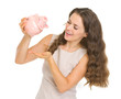 Happy young woman shaking out coins from piggy bank