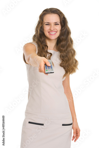 Happy young woman switching channels with tv remote control