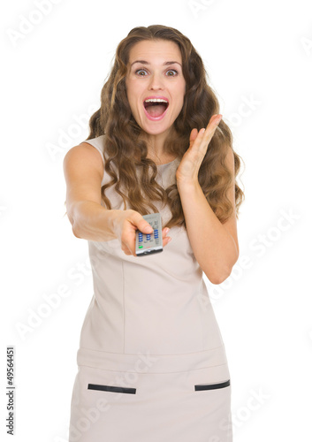 Surprised young woman with tv remote control