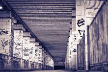 Spacer z kolumnami malowane w czarno-białe graffiti,