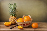 Still life with pineapple and tangerines on wooden table
