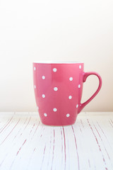 Polka dots cup on white wooden table over bright background