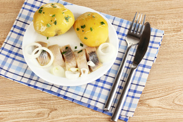 Dish of herring and potatoes on plate on wooden table close-up