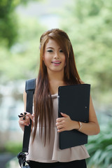 Young woman in business attire, carrying briefcase and holding f