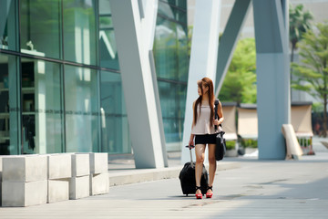 Young business woman walking outside of shopping plaza with her