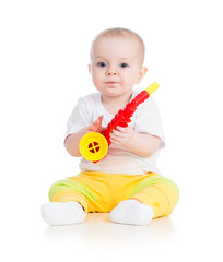 Funny baby girl playing musical toy. Isolated on white bac