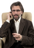 angry businessman sitting with mobile phone