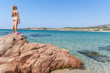 Bambina su scogli guarda il mare