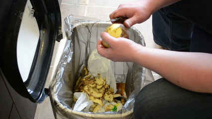 man hands peel potatoes. paring fall into waste bin