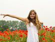 Den Sommer genießen / Junge Frau in Klatschmohnwiese