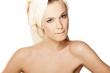 Scowling pretty girl with towel on head