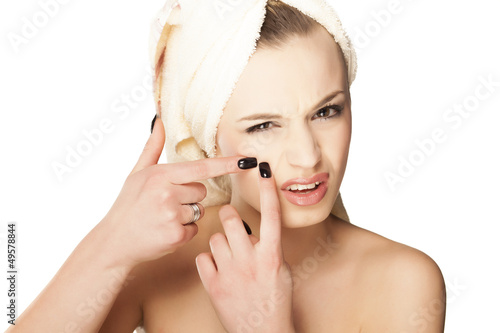 Scowling pretty girl squeezes her acne on her face