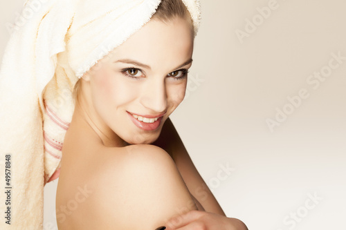 beautiful smiling young woman with a towel on her head
