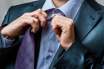 man in suit untying his neck tie