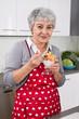 Ältere grauhaarige Dame isst einen Joghurt in der Küche