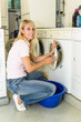 Frau befüllt eine Waschmaschine