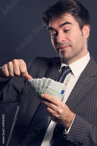 Geschäftsmann beim Geld scheffeln