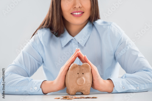 Happy business woman covering piggy bank with two hands - safety