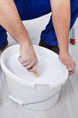 Worker stirring the paint - closeup on hands