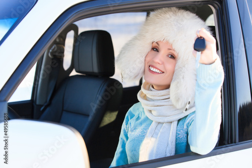 Happy woman in white fur hat in a car
