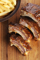 Grilled sliced barbecue pork ribs on a wooden background.