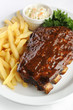 Grilled juicy barbecue pork ribs in a white plate with fries.