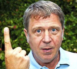 man in garden raises his finger to warn