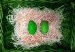 Pair easter green ecology eggs in  natural  wicker basket