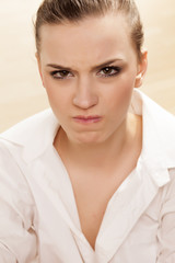 Scowling pretty girl posing in white shirt