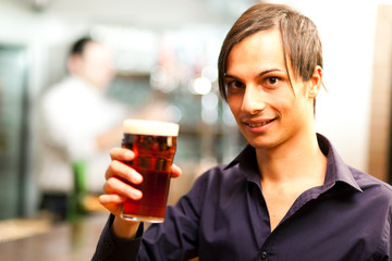 Young man having a drink in a bar