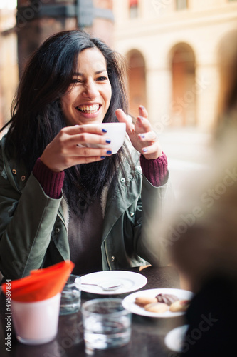 Young woman drinking coffee in a cafe outdoors.  - 49589834