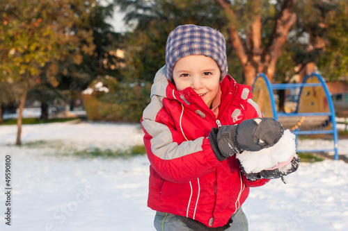 Young kid having fun in the snow with snowball.