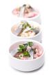 Drei Schalen Heringssalat in weißen Schalen