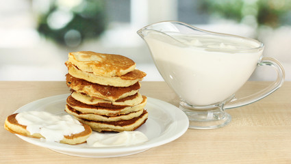 Sweet pancakes on plate with sour cream on table in kitchen