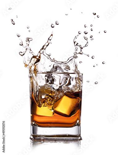 Fotobehang Alcohol whiskey splash with ice cubes isolated on white