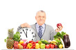 Mature man with red apple, clock and fruit and vegetables on a t