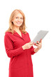 Mature smiling woman holding a tablet and looking at camera